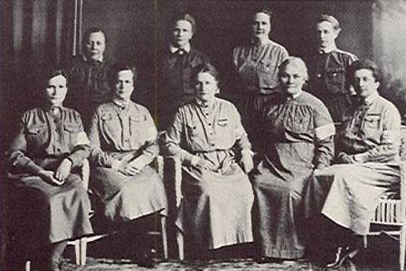 Kuva: Lotta Svärd-yhdistyksen keskusjohtokunta vuonna 1926. Istumassa vas. Hilja Riipinen, Signe Björkenheim, Helmi Arneberg-Pentti, Fanny Rikama ja Ruth Munck; seisomassa Hilma Pohjanpalo, Fanni Luukkonen, Tekla Brummer ja Fanny Munck Lotan ulkoisena tunnusmerkkinä oli harmaa lottapuku, johon kuuluivat valkoiset irtokaulukset ja -kalvosimet. sekä lottaneula Kaikki toimivat jäsenet antoivat lottalupauksen